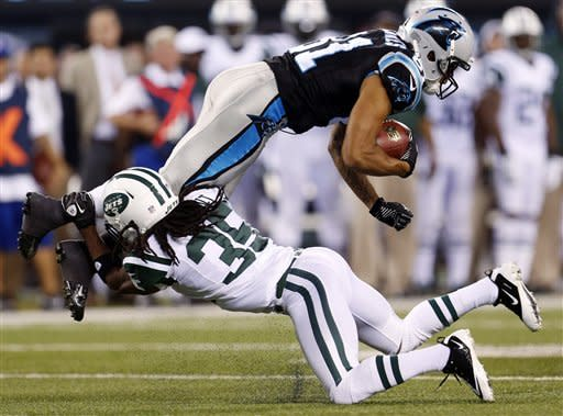 Carolina Panthers wide receiver Kealoha Pilares (81) is tackled by New York Jets cornerback Isaiah Trufant (35) during the first half of a preseason NFL football game, Sunday, Aug. 26, 2012, in East Rutherford, N.J. (AP Photo/Julio Cortez)