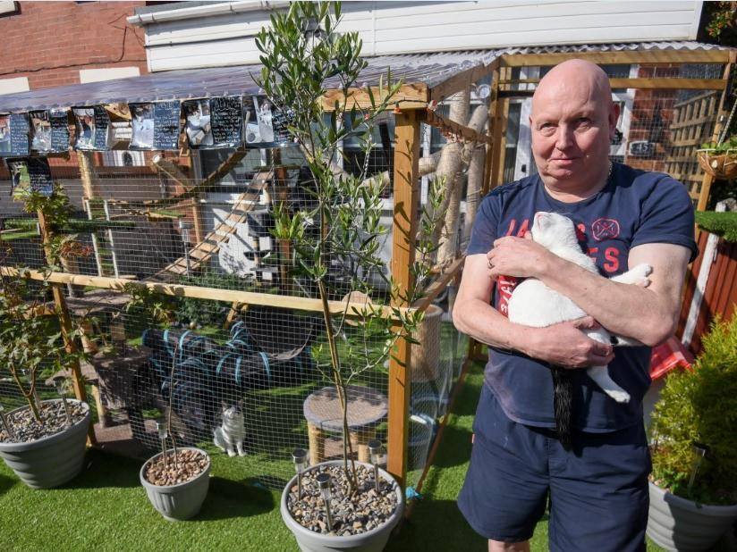 Adrian Marshall outside the catio. See SWNS story SWLEcat; A Blackpool couple who created a 'Jungle Jim's' inspired adventure playground for their ten cats may be forced to tear down the vast structure after neighbours complained to the council. Lorraine and Adrian Marshall, of Pedders Lane, built the enormous 'catio' in their front garden in June after losing three of their precious pets to road accidents outside their home. But they were visited by a Blackpool Council planning enforcement officer earlier this month and told that, because they had not obtained planning permission for the structure, it would have to come down.