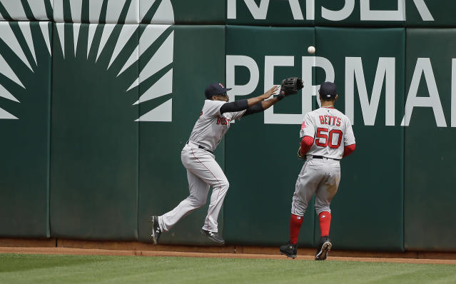 Boston Red Sox center fielder Jackie Bradley Jr., left, and right fielder Mookie Betts chase after a ball hit by the Oakland Athletics' Stephen Piscotty in the fourth inning of a baseball game Thursday, April 4, 2019, in Oakland, Calif. Piscotty hit a ground rule double and two runs scored on the play. (AP Photo/Eric Risberg)