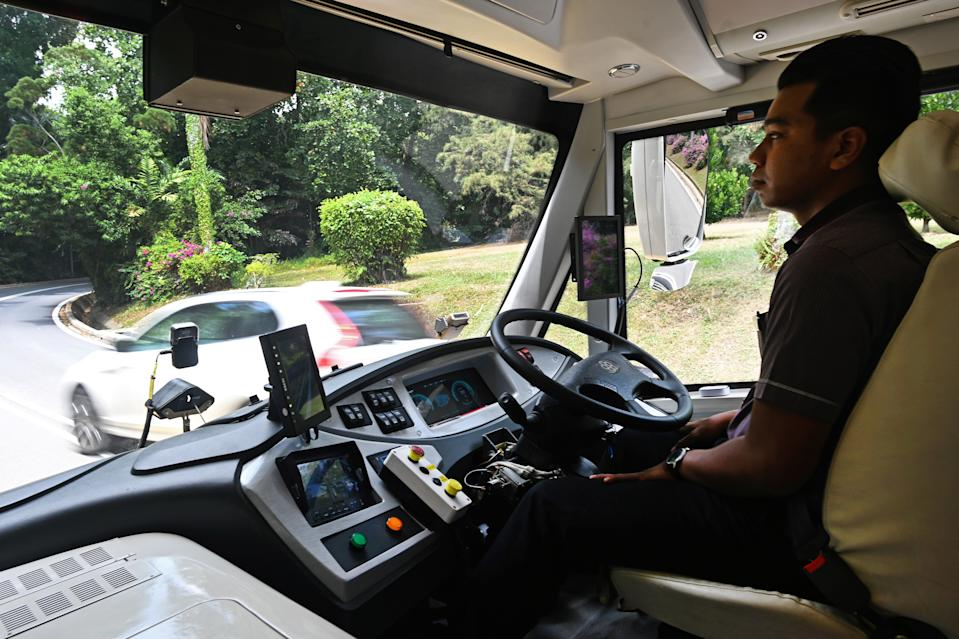 A safety driver sits in a moving on-demand autonomous shuttle bus during the official launch of a public trial run at Sentosa island resort in Singapore on August 20, 2019. - Singapore will next week begin a public trial of driverless buses that can be booked with an app, part of ambitions to roll out autonomous vehicles across the city-state. (Photo by Roslan RAHMAN / AFP)        (Photo credit should read ROSLAN RAHMAN/AFP/Getty Images)