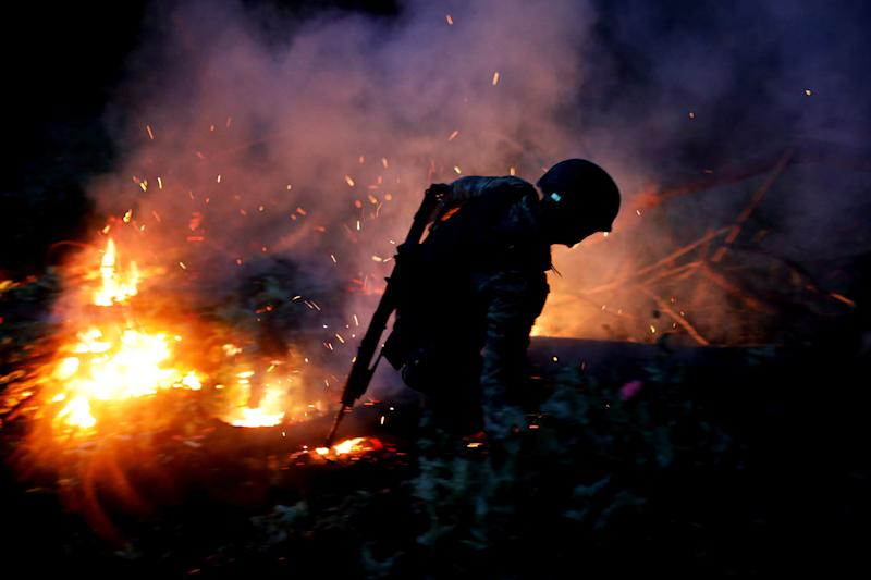 A soldier burns an illegal opium plantation