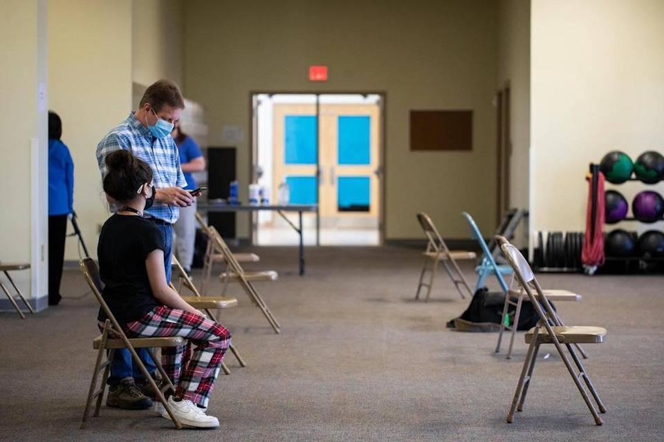Katie Carter, 12, waits with her father after receiving her first COVID-19 vaccination shot at STEAM Academy in Lexington, Ky., Thursday, May 13, 2021. Close to 60 children 12 and up where scheduled to receive the vaccine at STEAM Academy today.