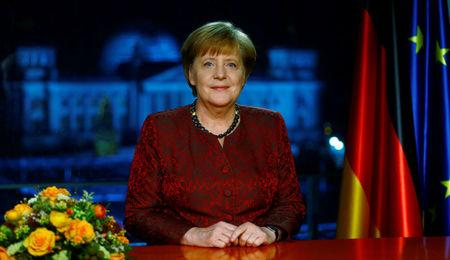 German acting Chancellor Merkel poses for photographs after the television recording of her annual New Year's speech at the Chancellery in Berlin