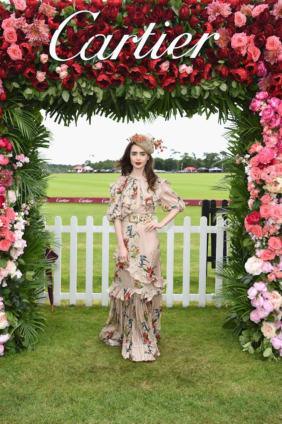 <p>Lily Collins attended the Cartier Queen's Cup Polo at Guards Polo Club on June 17 in a ruffled floral dress and co-ordinating fascinator. [Photo: Getty] </p>