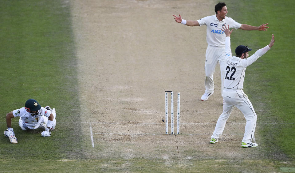 Pakistan captain Mohammad Rizwan, left, is run out after a direct throw by Mitchell Santner, not pictured, as Trent Boult and Kane Williamson, right, appeal during play on day three of the first cricket test between Pakistan and New Zealand at Bay Oval, Mount Maunganui, New Zealand, Monday, Dec. 28, 2020. (Andrew Cornaga/Photosport via AP)