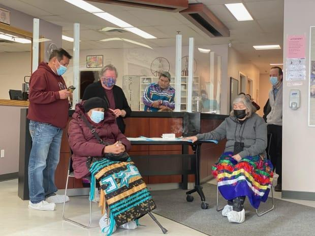 Masked Kehewin Cree Nation elders pray at a ceremony marking the arrival of COVID-19 vaccine doses in the northern Alberta community on Feb. 8, 2021. Kehewin council member Greyeagle Cardinal looks on from behind plexiglass.