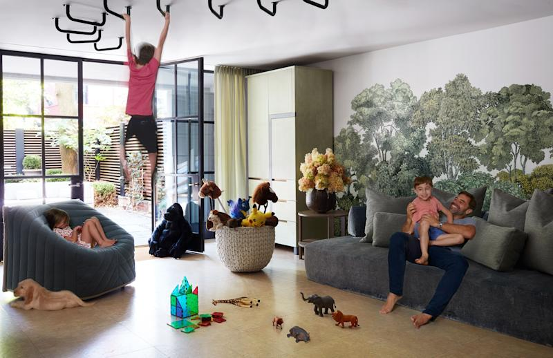 A mural by Rebel Walls decorates the play area. Sofa by Francesco Binfaré for Edra; custom cabinet; room & board side table; chair by Perrine Vigneron & Gilles Belley for Sancal.