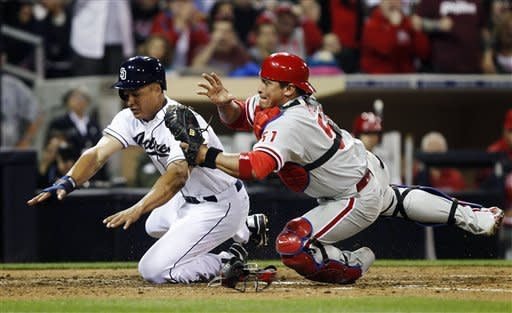 Philadelphia Phillies catcher Carlos Ruiz holds on to the ball after colliding at home plate with San Diego Padres' Will Venable, who was the second out on a double play in which Padres' Jeremy Hermida struck out and Venable was out stealing, in the sixth inning of a baseball game Thursday, April 19, 2012, in San Diego. (AP Photo/Lenny Ignelzi)