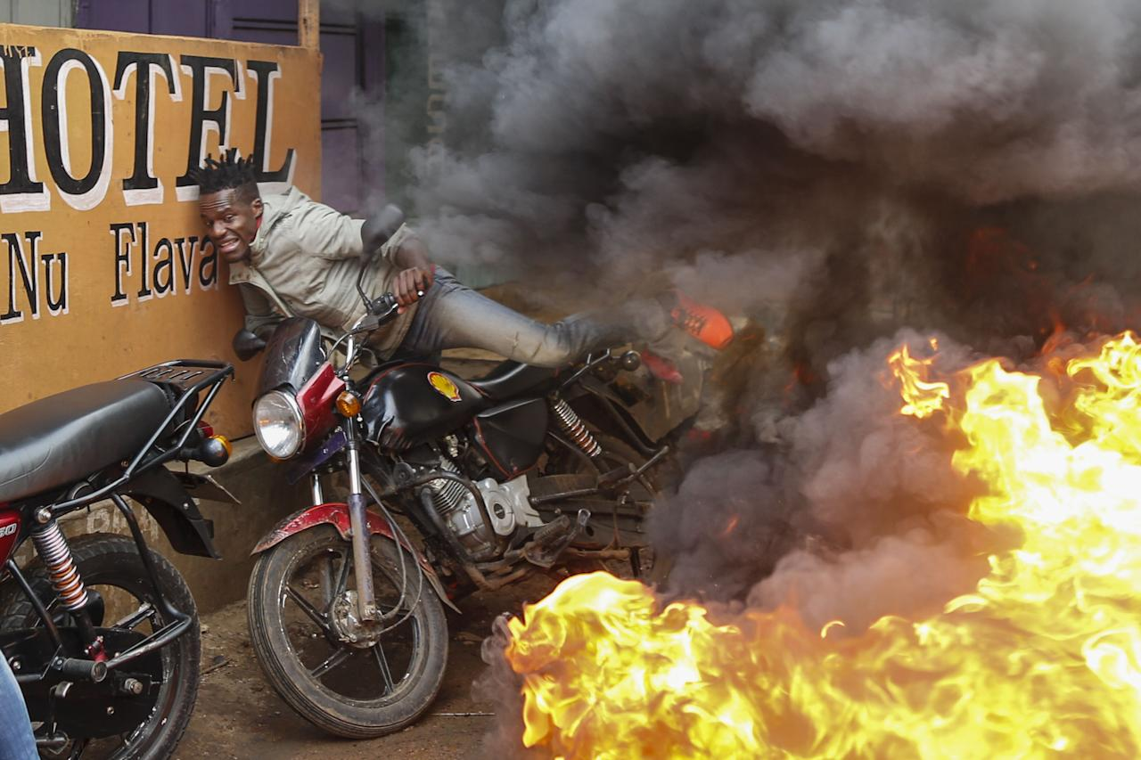 <p>A man falls from his motorbike as he tries to pass through a burning barricade set up by supporters of the opposition coalition the National Super Alliance (NASA) and its presidential candidate Raila Odinga to block vehicles from delivering electoral materials to the polling stations in other areas in Kibera slum, one of the opposition strongholds in Nairobi, Kenya, Oct. 25, 2017. (Photo: Dai Kurokawa/EPA-EFE/REX/Shutterstock) </p>