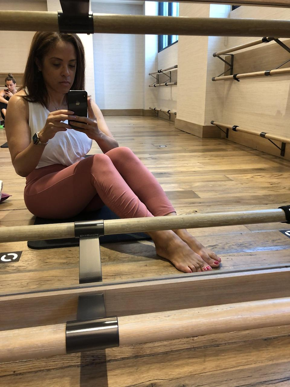 """<p>While I often like pants with high compression, unless the fit is just right, they roll at the waist or constrict too much for mat-based exercises. This pair's top stayed up no matter how I moved, and the light compression wasn't uncomfortable, even during the abs portion of class.</p> <p>In fact, these moisture-wicking <a href=""""https://www.popsugar.com/fitness/best-old-navy-go-dry-workout-clothes-for-women-48417375"""" class=""""link rapid-noclick-resp"""" rel=""""nofollow noopener"""" target=""""_blank"""" data-ylk=""""slk:GoDry leggings"""">GoDry leggings</a> are made mainly of cotton jersey so they feel like a thick, soft tee, but they still passed my squat test as they're not sheer at all. Of course, I'm never mad at a hidden pocket (which easily fits a phone and keys), either.</p> <p>The <span>petite one I selected</span> hit my leg right where 7/8 leggings should, but the bottom can also be scrunched up a little more for someone shorter. And if I'm being totally honest, the real reason I love these most for barre in particular is that I can check out that very ruched ankle detail while I'm confirming my foot placement in the mirror . . . and they look just as cute with slides when I head home, too.</p>"""