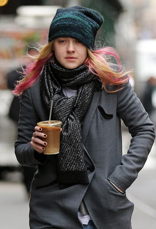 Actress Dakota Fanning, with pink dyed hair and ripped jeans, a gray overcoat, charcoal scarf, blue knit cap and suede boots, picks up a coffee at Balthazar on a snowy-day in SoHo, New York City. 