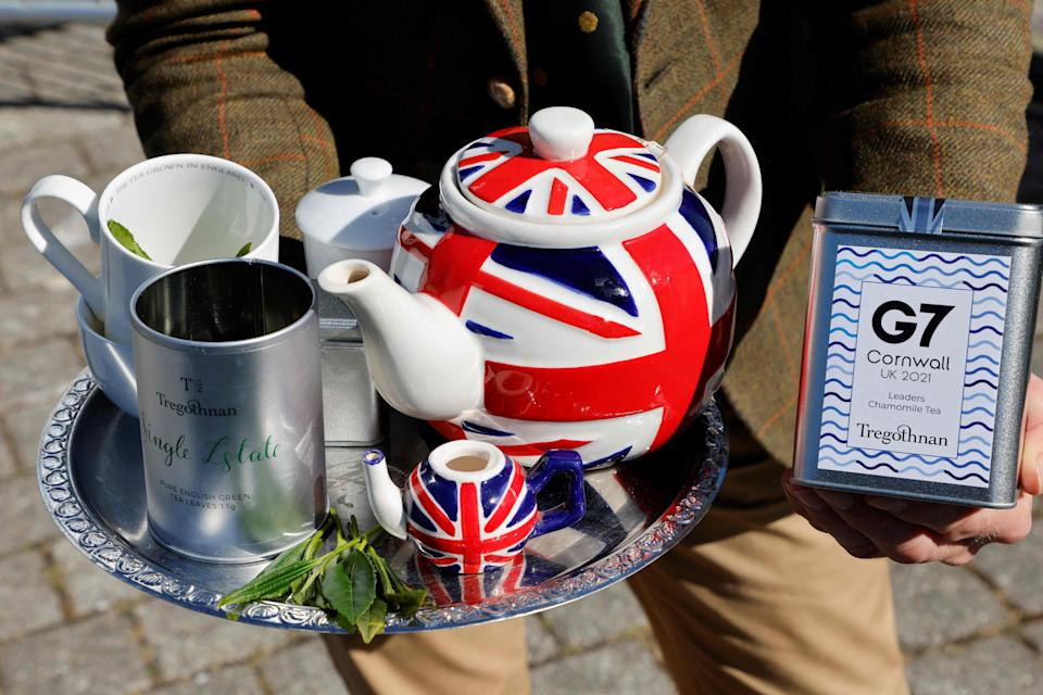 A man poses with a tea set outside the G-7 media center in Falmouth, Cornwall during the G7 summit on June 13, 2021.