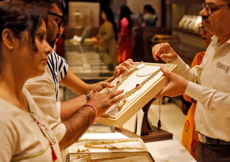 A salesman shows a gold necklace to customers at a jewellery showroom in Ahmedabad