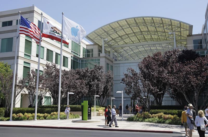 People walk by the Apple headquarters in Cupertino, Calif., Monday, Aug. 20, 2012. On Monday, Aug. 20, 2012, Apple set a new record for the most valuable company at $621 billion, beating Microsoft's 1999 high. (AP Photo/Paul Sakuma)
