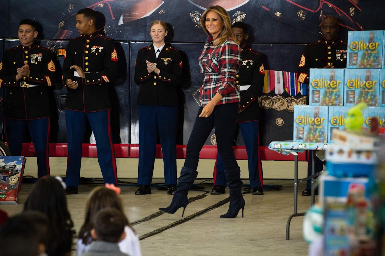 <p>The First Lady paired plaid button-down jacket by Tomas Maier with skinny jeans and navy slouchy stiletto boots to attend a Toys for Tots event at Joint Base Anacostia-Bolling. </p>