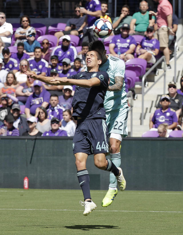 Orlando City's Joao Moutinho (44) goes up against Vancouver Whitecaps' Erik Godoy (22) for a header during the first half of an MLS soccer match, Saturday, April 20, 2019, in Orlando, Fla. (AP Photo/John Raoux)