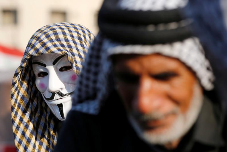Demonstrator wears a mask, as he takes part during the ongoing anti-government protests in Baghdad