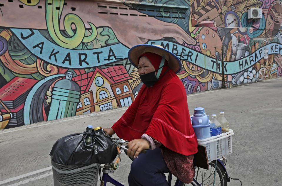 """A traditional herbal drink vendor wearing a mask to help curb the spread of the coronavirus outbreak cycles past a mural with writings that read """"Jakarta gives without expecting anything in return,"""" in Jakarta, Indonesia, Tuesday, Aug. 4, 2020. (AP Photo/Dita Alangkara)"""