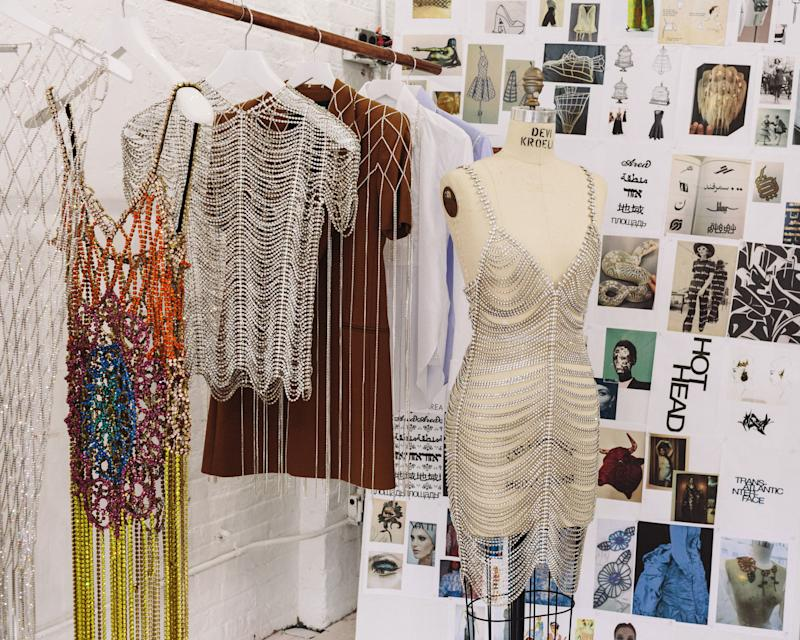 Crystal pieces hang in front of a mood board