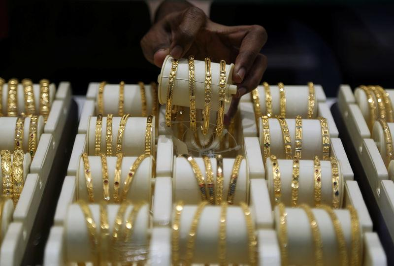 A salesman arranges gold bangles inside a jewellery showroom on the occasion of Akshaya Tritiya, a major gold buying festival, in Mumbai