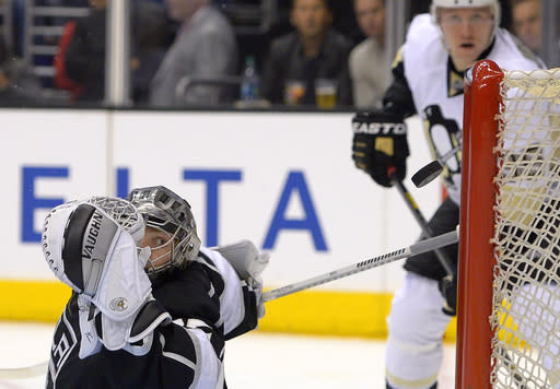 Los Angeles Kings goalie Jonathan Quick, left, is scored on by Pittsburgh Penguins left wing Chris Kunitz as Penguins left wing Jussi Jokinen, right, of Finland, watches during the first period of an NHL hockey game, Thursday, Jan. 30, 2014, in Los Angeles. (AP Photo)