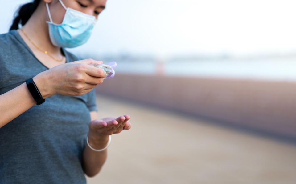 woman using hand sanitizer on the street and wearing face mask as a covid 19 precaution outdoors
