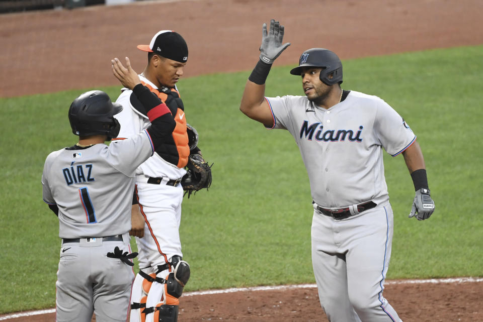 Miami Marlins' Jesus Aguilar, right, is greeted at home plate by Isan Diaz (1) after hitting second-inning home run off Baltimore Orioles starting pitcher Jorge Lopez during a baseball game Wednesday, July 28, 2021, in Baltimore. (AP Photo/Terrance Williams)