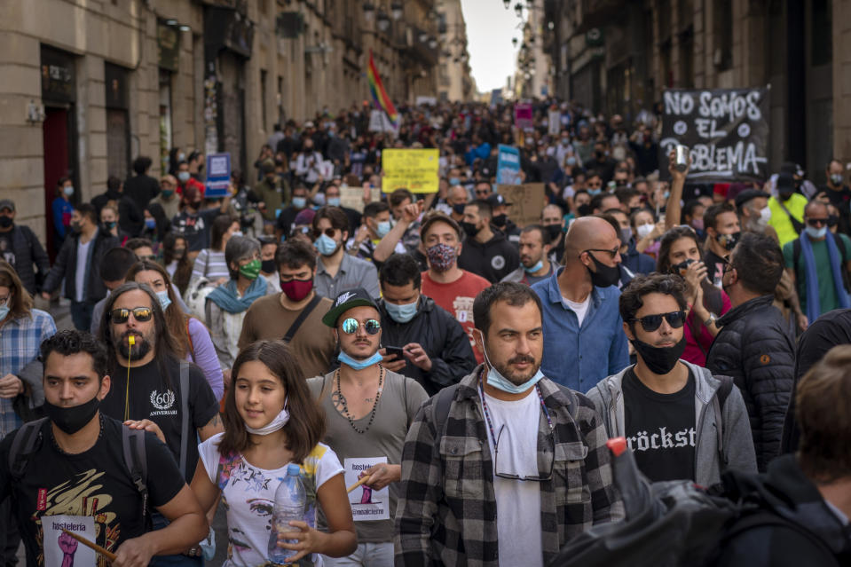 """Workers of several sectors including restaurants, bars, hotel, taxi, and nightclubs march during a protest against the latest virus restrictions in Barcelona, Spain, Wednesday, Oct. 28, 2020. Since Oct. 14 bars and restaurants have been closed, allowed to serve food and drink for take-away and delivery only. On Sunday a curfew from 10p.m. to 6 a.m. was imposed. Still, virus cases are surging and Catalan authorities are now considering even more restrictions including weekend lockdowns. Banner reads in Spanish """"we want to work"""". (AP Photo/Emilio Morenatti)"""