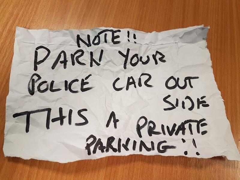 An angry resident left this note on the windscreen of a police car responding to a 999 call. (PA).