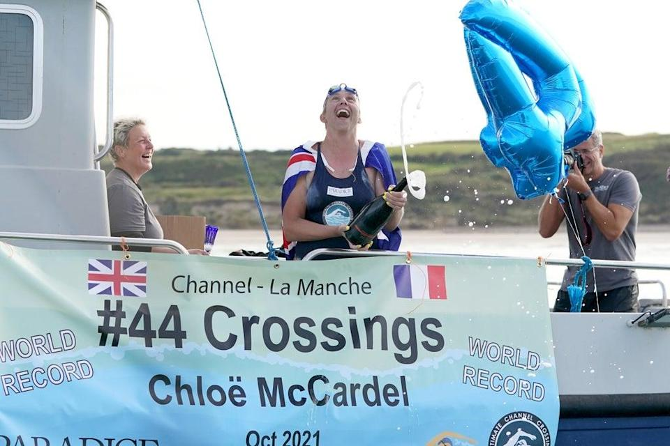 Chloe McCardel pops the cork on a bottle of champagne after completing her swim across the English Channel for a 44th time and breaking the world record (Gareth Fuller/PA) (PA Wire)