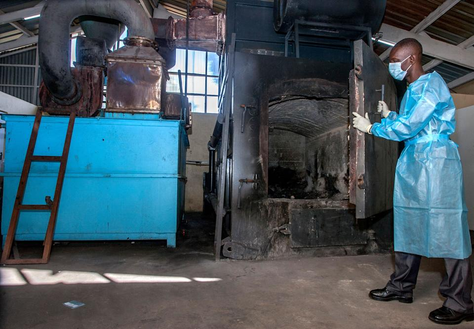 A pharmaceutical incinerator operator opens the door to prepare the machine to burn expired Covid-19 Astra Zeneca vaccines at Malawis main referral hospital, Kamuzuz Central Hospital in Lilongwe on May 19, 2021. - Malawi has destroyed nearly 17,000 doses of the AstraZeneca vaccine that had expired in mid-April, with the health minister blaming