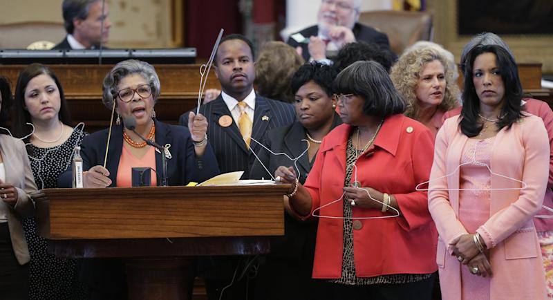 Rep. Senfronia Thompson, D-Houston, second from left, holds a coat hangar as she stands with fellow representatives while proposing an amendment to the second reading of HB 2, legislation that will restrict abortion rights, on the Texas House floor,Tuesday, July 9, 2013, in Austin, Texas. The Texas House is expected to vote on the bill Tuesday. (AP Photo/Eric Gay)