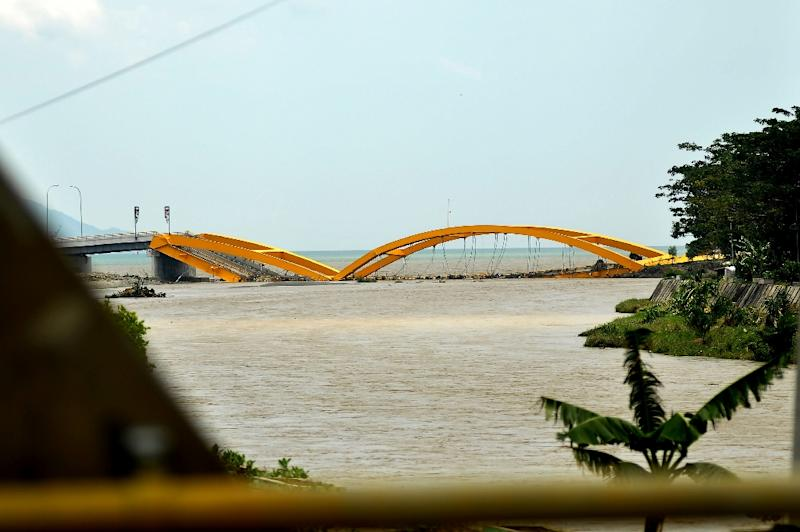 Images showed a double-arched yellow bridge had collapsed with its two metal arches twisted as cars bobbed in the water below (AFP Photo/OLA GONDRONK)