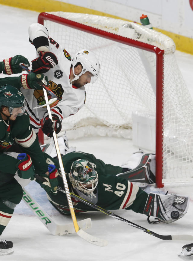 Minnesota Wild goalie Devan Dubnyk, right, makes a glove save as Chicago Blackhawks' Artem Anisimov, left, of Russia, positions himself at the net during the first period of an NHL hockey game Thursday, Oct. 11, 2018, in St. Paul, Minn. (AP Photo/Jim Mone)