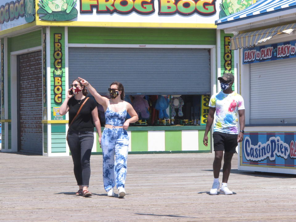 People wearing masks walk on the boardwalk in Seaside Heights, N.J. on Friday, May 15, 2020, the on the first day it opened during the coronavirus outbreak. It and another popular Jersey Shore beach, Point Pleasant Beach, were among those allowing people back onto the sand with some restrictions to try to slow the spread of the virus. (AP Photo/Wayne Parry)