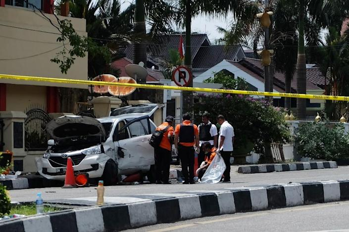 Indonesian policemen examine a car used by attackers during an assault on a police headquarters on the island of Sumatra that left one officer dead and two wounded (AFP Photo/DEDY SUTISNA)