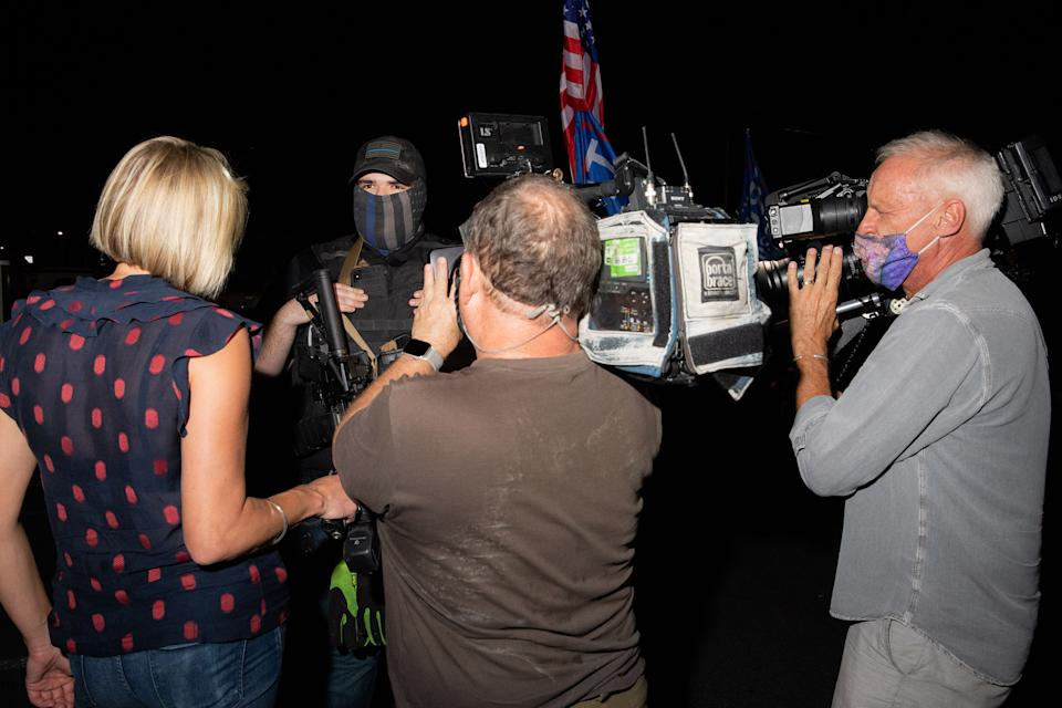 """A member of a militia is flanked by cameras at the Maricopa County Elections office in Phoenix, on Nov. 5<span class=""""copyright"""">Sinna Nasseri for TIME</span>"""