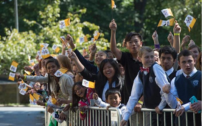 School children and parents cheer while waiting for Pope Francis at the Apostolic Nunciature to the United States on September 23, 2015 in Washington, DC (AFP Photo/Molly Riley)