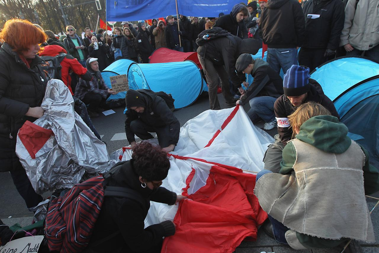 "BERLIN, GERMANY - NOVEMBER 12:  Demonstrators protesting against the world financial system hastily set up tents on a street near the Brandenburg Gate during a march on November 12, 2011 in Berlin, Germany. Inspired by the ""Occupy Wall Street"" protests in the USA, similar protests have been taking place across Germany, especially in Berlin and Frankfurt, for weeks.  (Photo by Sean Gallup/Getty Images)"