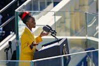 """<p>Amanda Gorman delivered her poem <em>The Hill </em><em>We Climb</em> for the Inauguration dressed in <a href=""""https://www.prada.com/us/en.html"""" rel=""""nofollow noopener"""" target=""""_blank"""" data-ylk=""""slk:Prada"""" class=""""link rapid-noclick-resp"""">Prada</a>, a house with whom she has collaborated in the past. A double-breasted coat in an uplifting shade of yellow, red satin headband, and classic white poplin shirt and black pencil skirt deliver a polished look much like the reading Gorman gave. </p><p>Gorman accessorized the outfit with a pair of <a href=""""https://go.redirectingat.com/?id=74968X1525071&xs=1&url=https%3A%2F%2Fwww.neimanmarcus.com%2Fc%2Fdesigners-nikos-koulis-cat69360749&sref=https%3A%2F%2Fwww.cosmopolitan.com%2Fstyle-beauty%2Ffashion%2Fa35268214%2Famanda-gorman-biden-inauguration-poet-outfit%2F%3Futm_campaign%3Dlikeshopme%26utm_content%3Dwww.instagram.com%2Fp%2FCKR1uI1BpsG%2F%26utm_medium%3Dinstagram%26utm_source%3Ddash%2520hudson&xcust=%5Butm_source%7Cdash+hudson%5Butm_campaign%7Clikeshopme%5Butm_medium%7Cinstagram%5Bgclid%7C%5Bmsclkid%7C%5Bfbclid%7C%5Brefdomain%7Clikeshop.me%5Bcontent_id%7C64496347-a428-4130-963b-6771e991df3c%5Bcontent_product_id%7C%5Bproduct_retailer_id%7C"""" rel=""""nofollow noopener"""" target=""""_blank"""" data-ylk=""""slk:Nikos Koulis"""" class=""""link rapid-noclick-resp"""">Nikos Koulis</a> gold hoop earrings with a hanging diamond and a birdcage ring by <a href=""""https://go.redirectingat.com/?id=74968X1525071&xs=1&url=https%3A%2F%2Fwww.modaoperandi.com%2Fwomen%2Fdesigner%2Fof-rare-origin&sref=https%3A%2F%2Fwww.cosmopolitan.com%2Fstyle-beauty%2Ffashion%2Fa35268214%2Famanda-gorman-biden-inauguration-poet-outfit%2F%3Futm_campaign%3Dlikeshopme%26utm_content%3Dwww.instagram.com%2Fp%2FCKR1uI1BpsG%2F%26utm_medium%3Dinstagram%26utm_source%3Ddash%2520hudson&xcust=%5Butm_source%7Cdash+hudson%5Butm_campaign%7Clikeshopme%5Butm_medium%7Cinstagram%5Bgclid%7C%5Bmsclkid%7C%5Bfbclid%7C%5Brefdomain%7Clikeshop.me%5Bcontent_id%7C64496347-a428-4130-963b-6771e991df3c%5Bcontent_pr"""