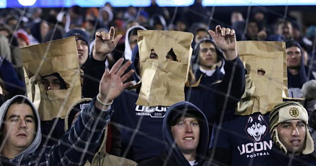 Connecticut Huskie fans wear paper bags over their heads during the first half of an NCAA college football game against Louisville, in East Hartford, Conn., Friday, Nov. 8, 2013. (AP Photo/Charles Krupa)