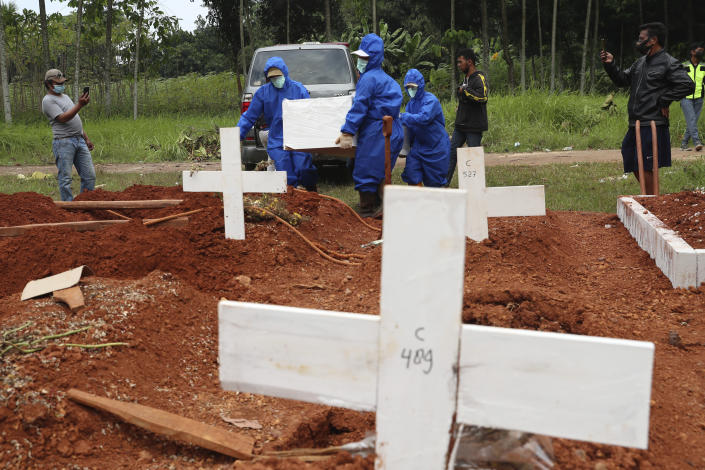 Workers in protective suits carry a coffin containing the body of a COVID-19 victim to a grave for a burial at Cipenjo cemetery in Bogor, West Java, Indonesia, Wednesday, July 14, 2021. The world's fourth most populous country has been hit hard by an explosion of COVID-19 cases that have strained hospitals on the main island of Java.(AP Photo/Achmad Ibrahim)