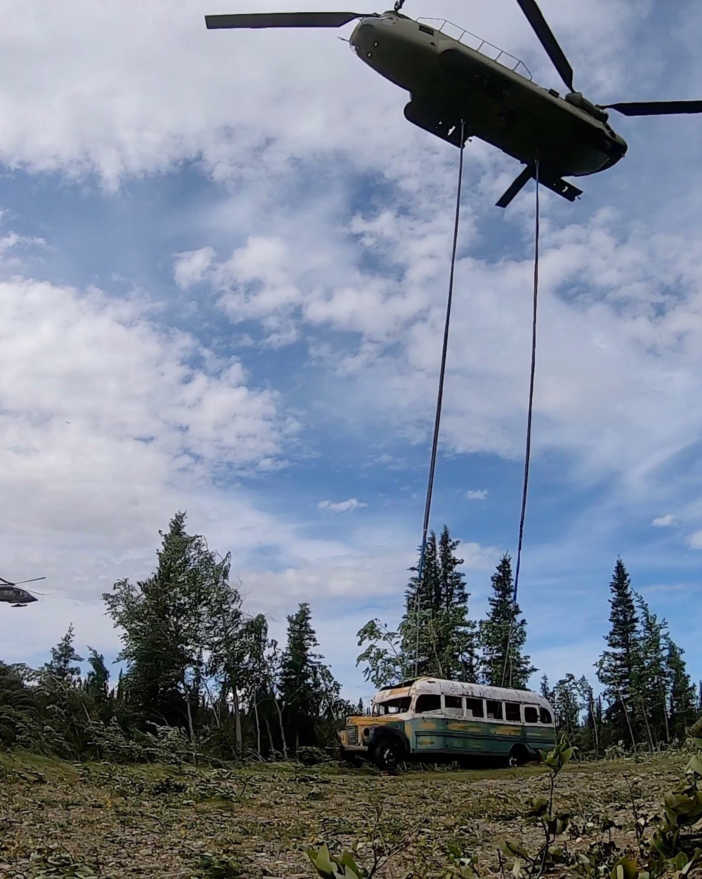 "In this photo released by the Alaska National Guard, Alaska Army National Guard soldiers use a CH-47 Chinook helicopter to removed an abandoned bus, popularized by the book and movie ""Into the Wild,"" out of its location in the Alaska backcountry Thursday, June 18, 2020, as part of a training mission. Alaska Natural Resources Commissioner Corri Feige, in a release, said the bus will be kept in a secure location while her department weighs various options for what to do with it. (Sgt. Seth LaCount/Alaska National Guard via AP)"
