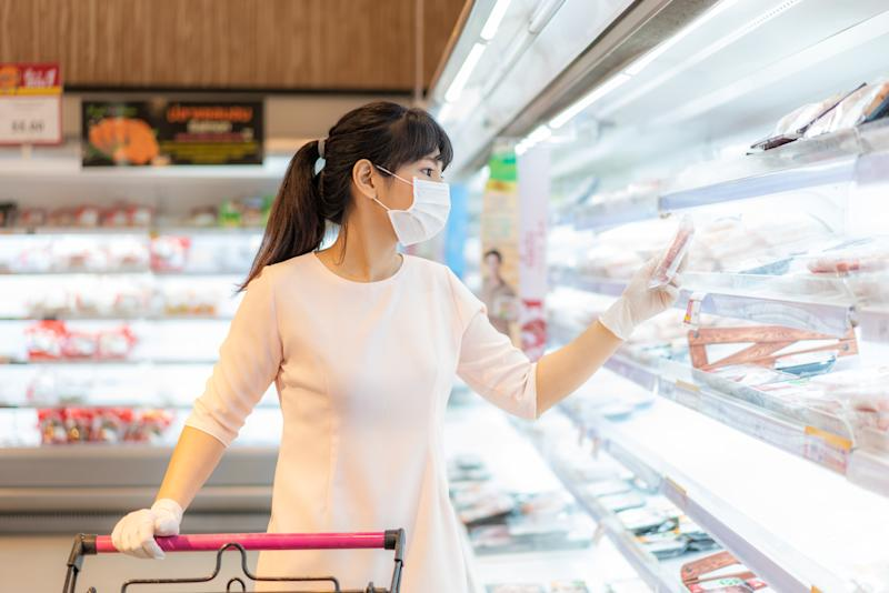 Asian woman with hygienic mask and rubber glove with shopping cart in grocery and looking for fresh meat pack to buy during covid-19 outbreak for preparation for a pandemic quarantine