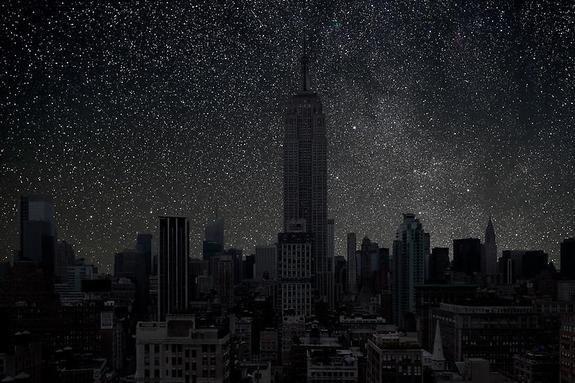 Starlight shines through the windows of the Empire State Building in this photo of a darkened New York City.
