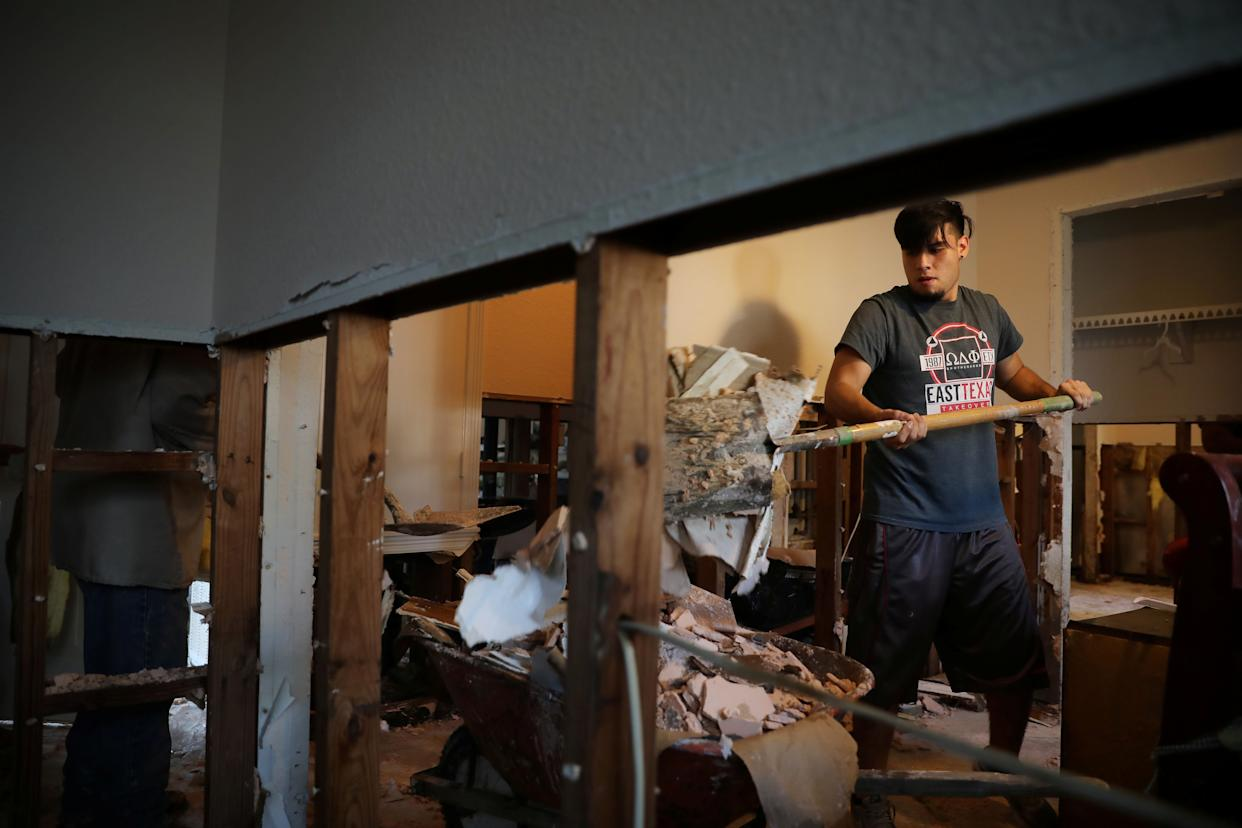 Lorenzo Salina helps a neighbor remove damaged walls.