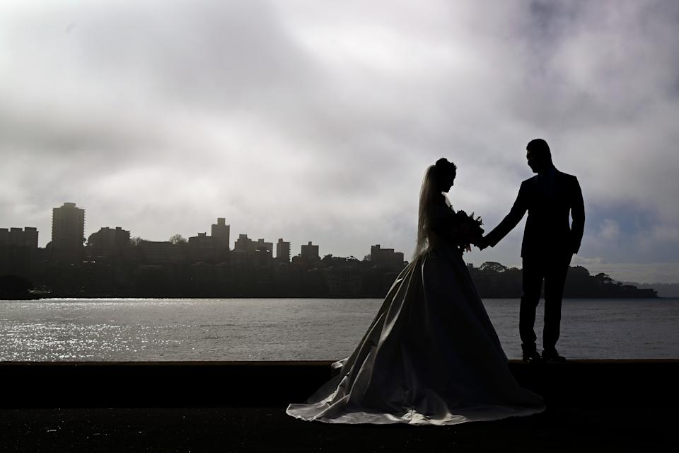 A couple pose for a wedding photo during morning fog in Sydney, Tuesday, May 19. Source: AAP