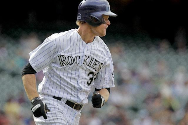 Colorado Rockies' Justin Morneau singles during the eighth inning of a baseball game against the Chicago White Sox, Wednesday, April 9, 2014, in Denver. The Rockies won 10-4. (AP Photo/Barry Gutierrez)