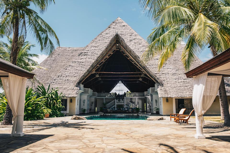 Looking into the lofty, open-air living room, from which a saltwater pool extends out to the terrace. The makuti thatched roof is composed of sun-dried coconut palm leaves hand-sewn into intricate layers.