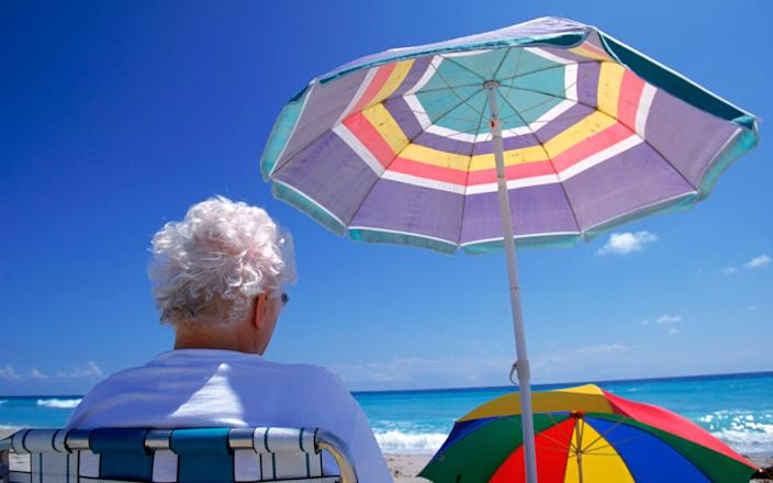 Elderly woman sits in the shade on a Florida beach - Getty